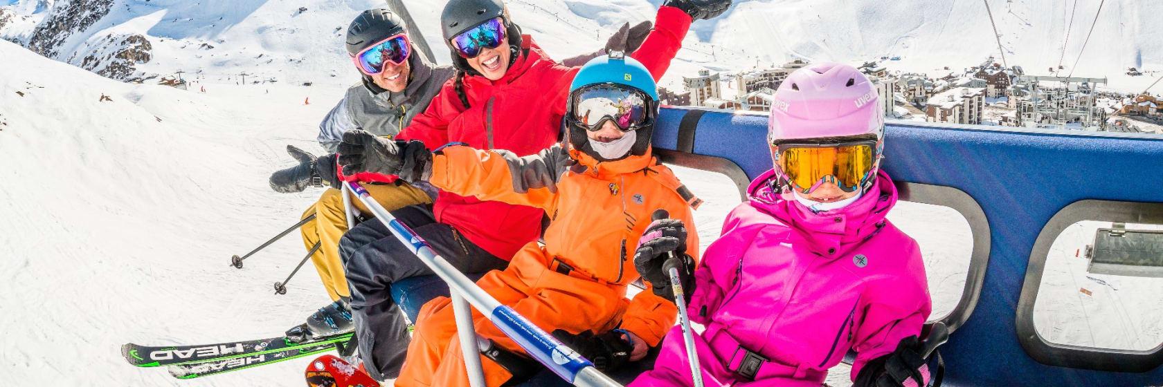 Glad familie på skiferie i lift med snebeklædte bjerge i baggrunden