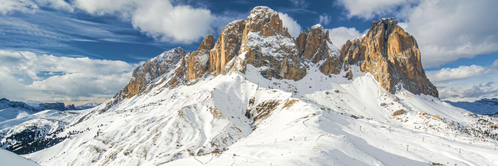 Pister og bjerge med sne og blå himmel med skyer i Canzei