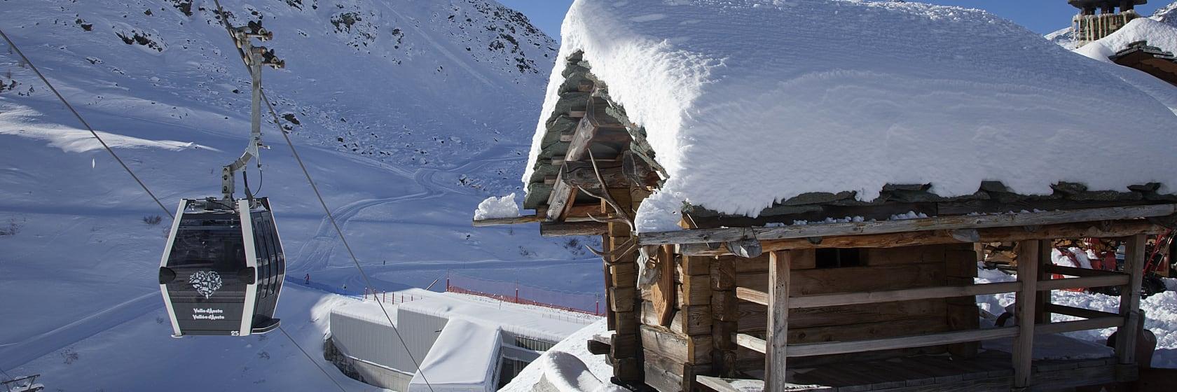 Skihytte med sne på taget i skiområde med skilift i Alperne