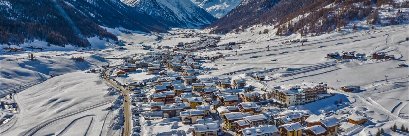 Skihytter i bjergene med sne på tagene i Livigno