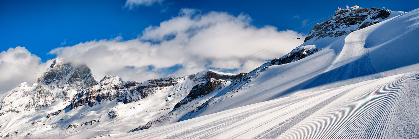 Smukt snelandskab i bjerge med blå himmel og enkelte skyer i La Rosière i Frankrig
