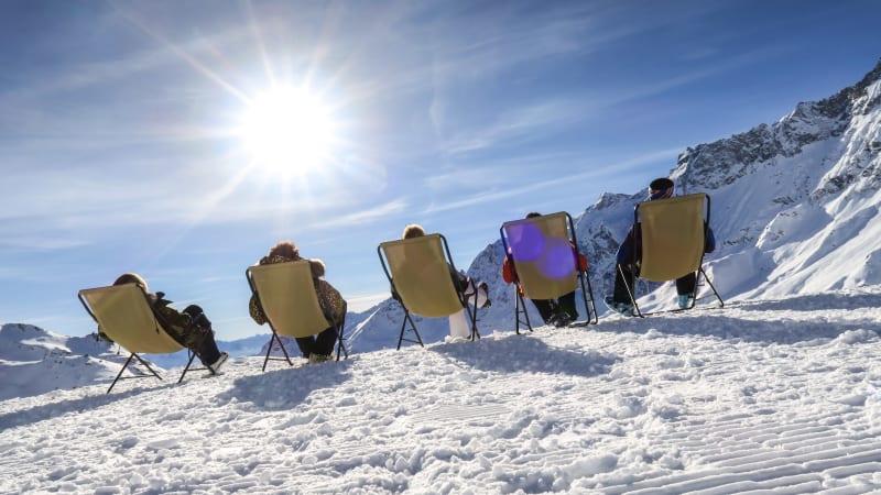 Mennesker i gule liggestole i sneen med blå himmel på skiferie i Cervinia