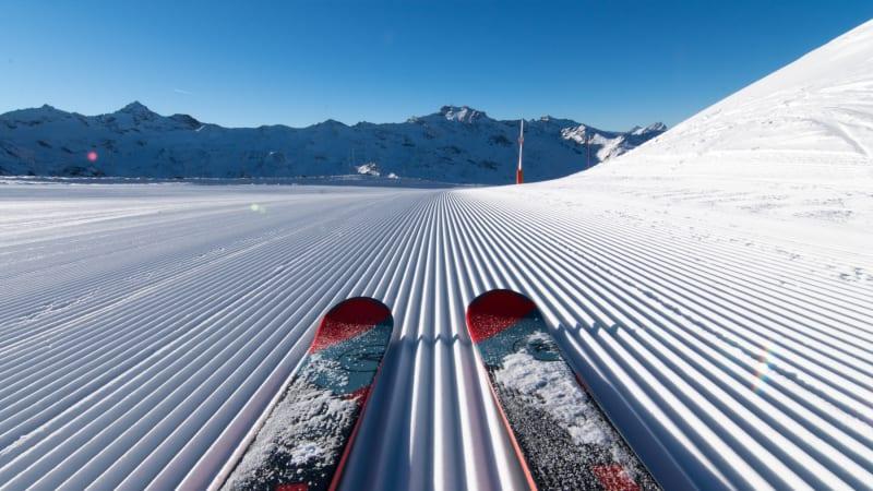 Ski på pisten med blå himmel i Val Thorens