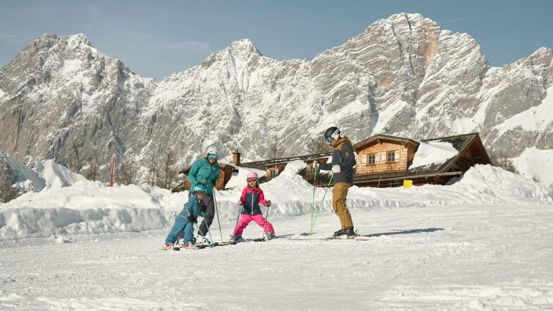 Forældre med to børn på ski i vinterferien med bjerge i baggrunden i Schladming