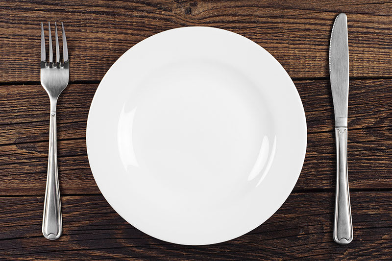 White plate with knife and fork on brown wood table