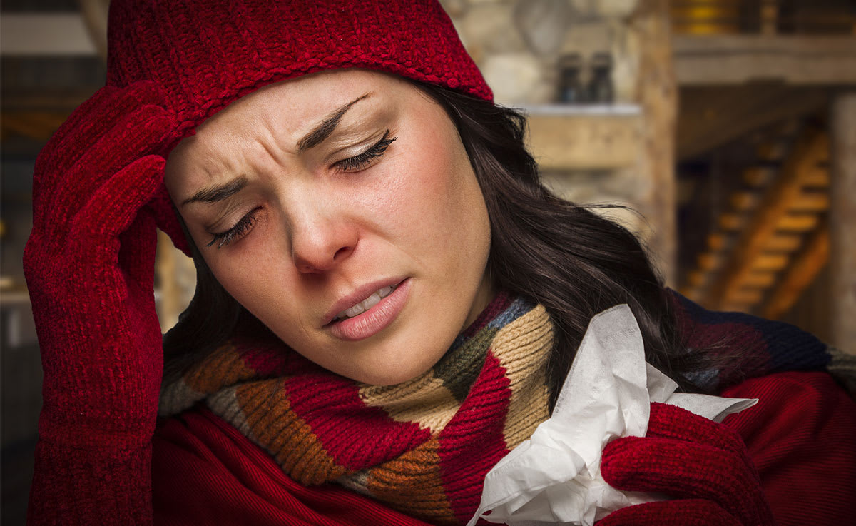 Woman with a cold wearing hat and mitts with red nose