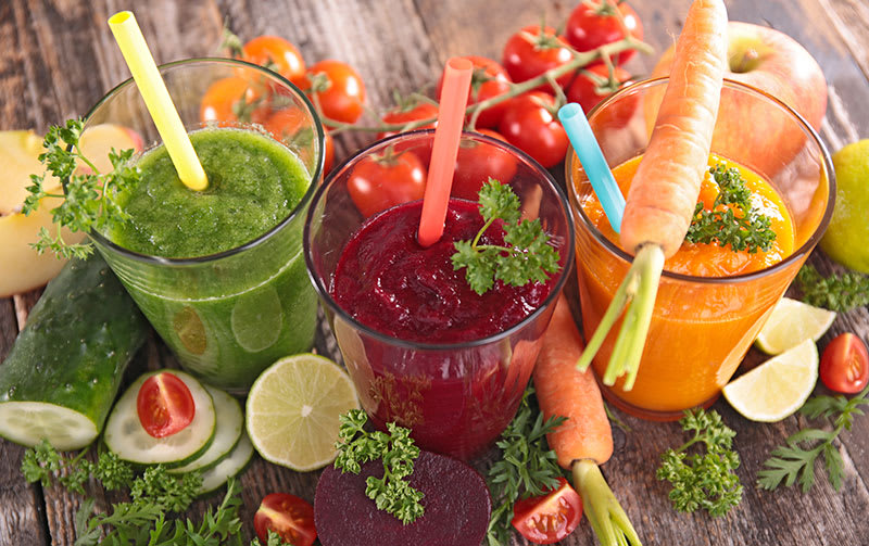 Cups filled with freshly pressed vegetable juices for healthy skin.