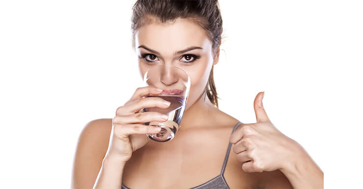 Woman giving thumbs up while she drinks water to lose weight.