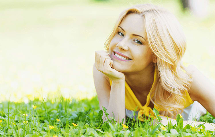 blonde woman lying on front in grass smiling with face resting in hand