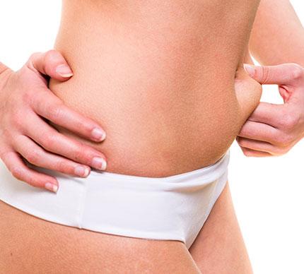 woman pinching stomach fat