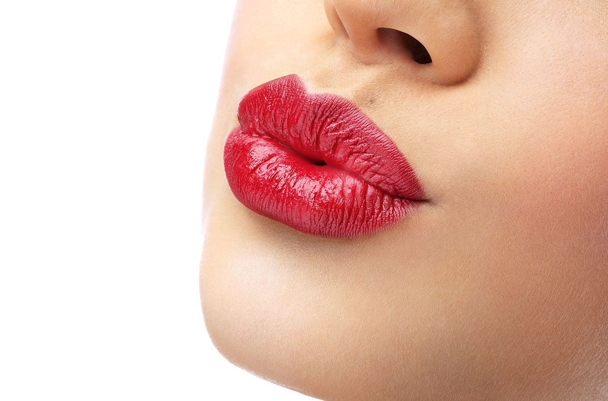 Woman's red lips pursed in a kiss.
