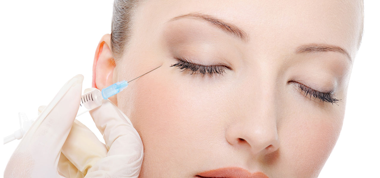 Woman getting botox injection near her eyes.