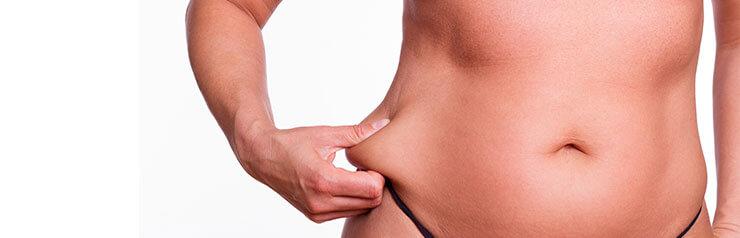 Woman pinching fat on waist and stomach.
