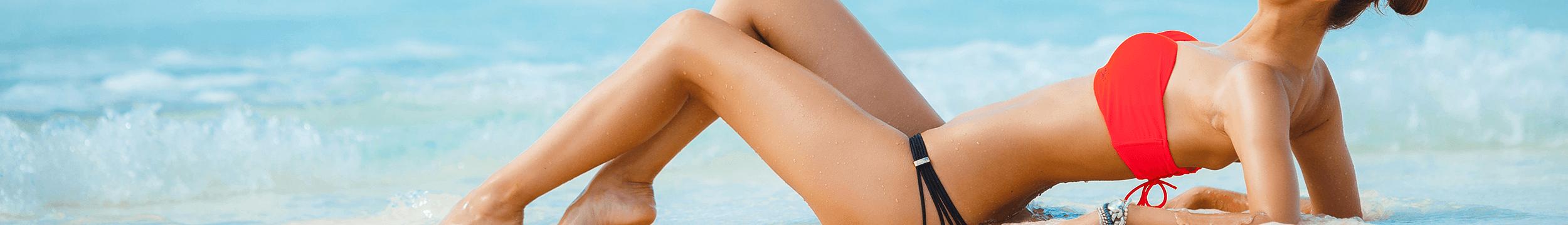 woman in red bikini top and black bottoms lying on beach