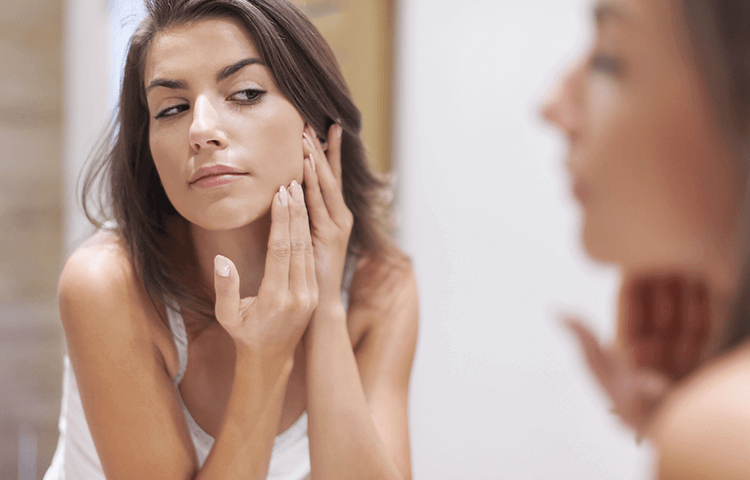 woman looking acne on her face in mirror