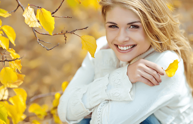 blonde woman in white sweater sitting beside tree in the autumn