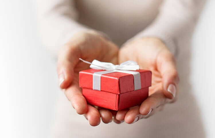 woman with small red gift box with white bow in her hands