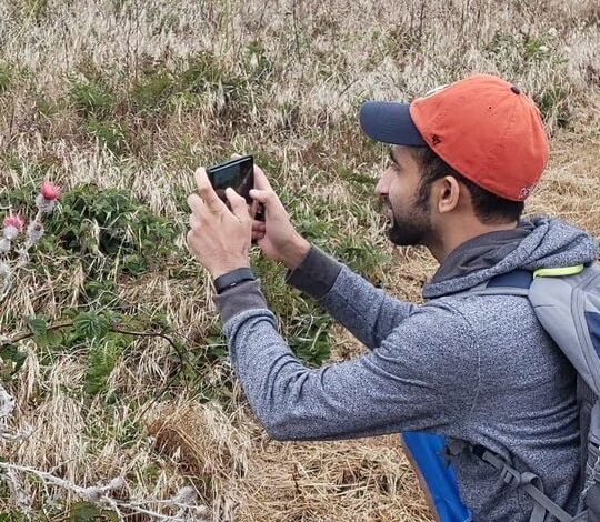 Saad wearing an orange Houston Astros hat, a grey backpack and a hoodie is pointing his cell phone at wildflowers to take a picture.