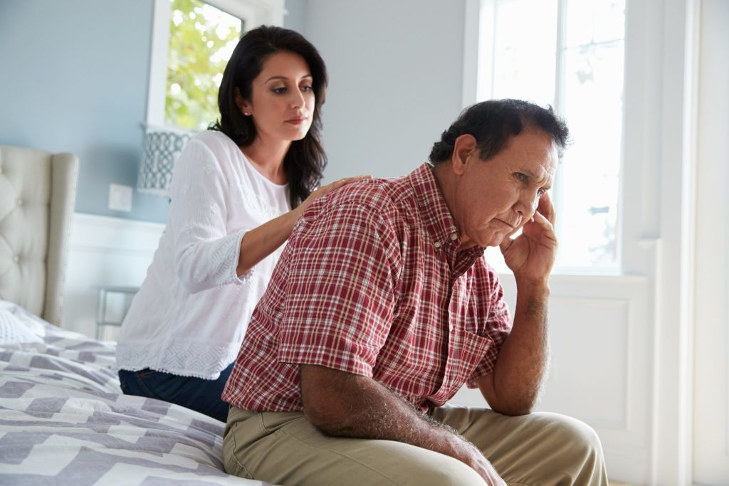 Adult Daughter Comforting Father Suffering With Alzheimers