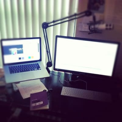 Desk with Laptop and secondary monitor with microphone in the background