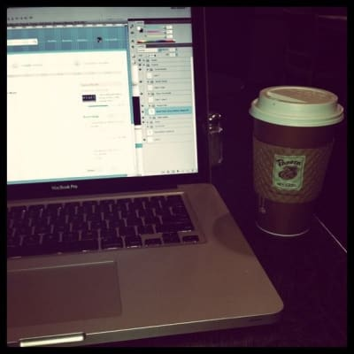 Photoshop appears on laptop screen next to coffee cup