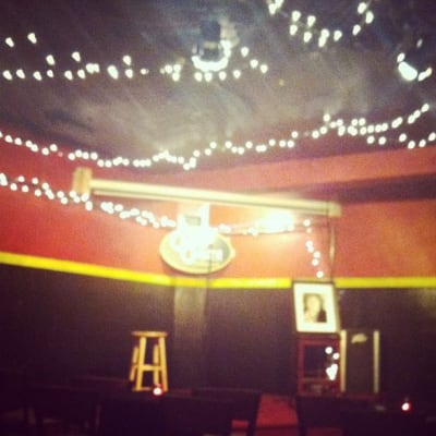 The stage at the comedy club lit with twinkle lights