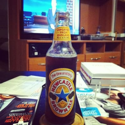 Newcastle beer sits on a coffee table with Conan in the background