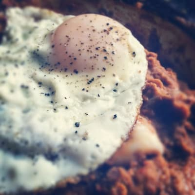 Over easy egg on top of refried pinto beans