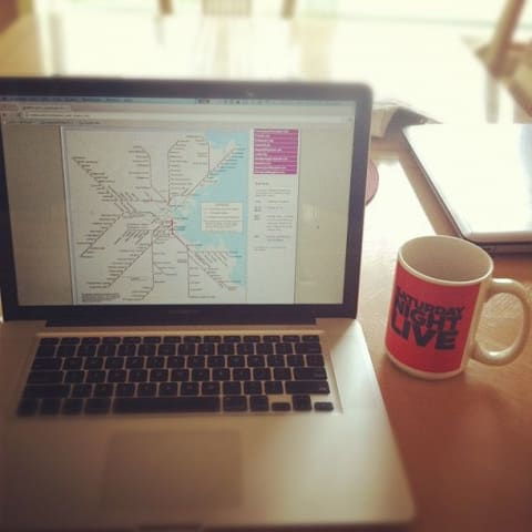Laptop with transit map on it, next to a coffee cup