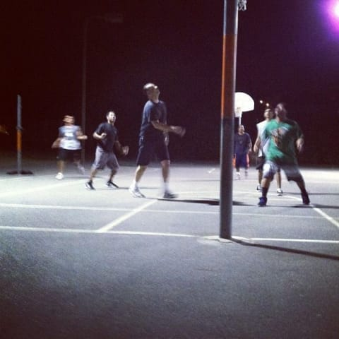 People look up to rebound basketball at park