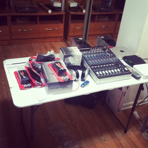 Table full of audio gear: mixer, cables, and routers