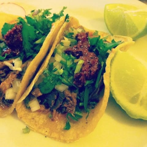 Two tacos next to some lime