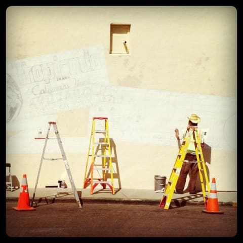 Ladders, paint and other supplies while a mural is sketched on a wall.