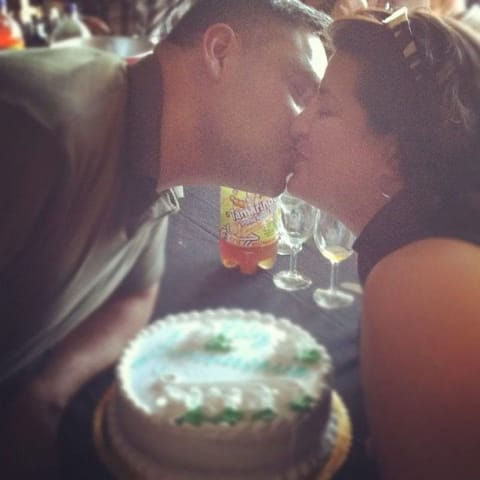My parents kissing in front of their anniversary cake