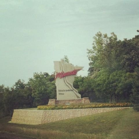 A sign in the shape of the state of Minnesota welcomes you