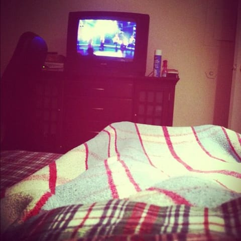 In bed, under the covers, watching TV