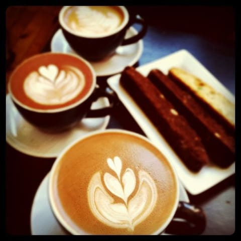 Three coffees with latte art, surrounded by biscotti