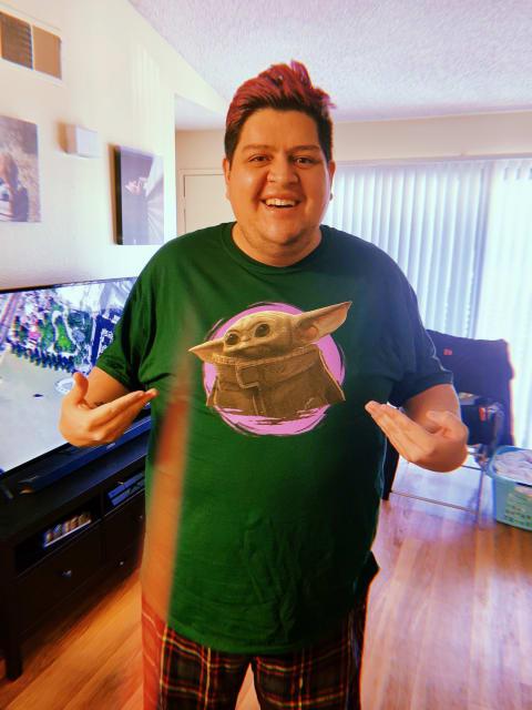 Me pointing at my new green Baby Yoda shirt