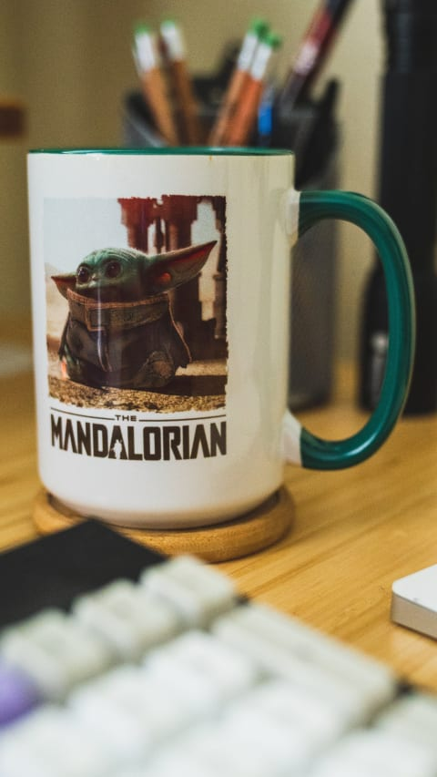 Mug with a green interior and handle with Baby Yoda and The Mandalorian logo beneath it