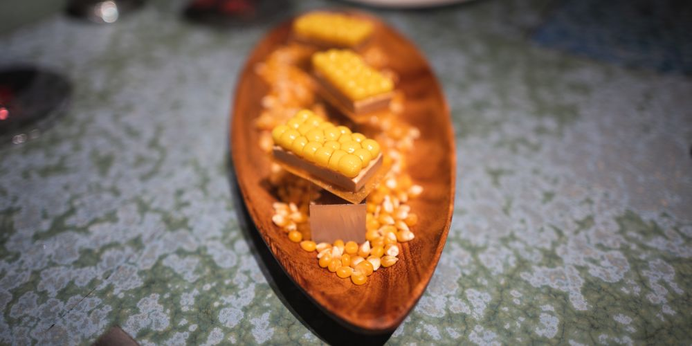 Corn on foie gras on a cracker on a bed of dried corn kernels