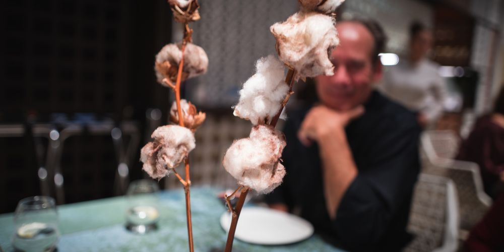 Puffy balls of cotton and cotton candy on a branch with a man staring in delight