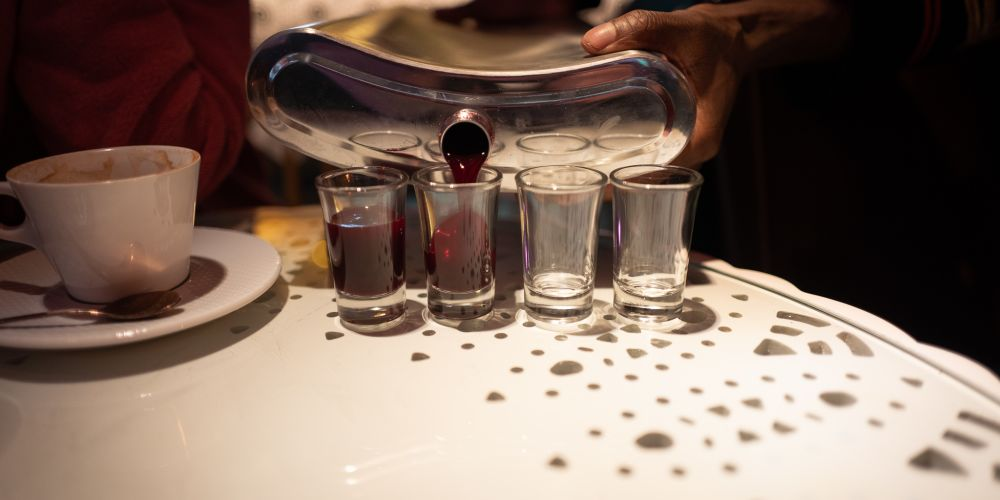 A flask, about 10 times the size of a regular flask pouring a deep red liquid into shot glasses.