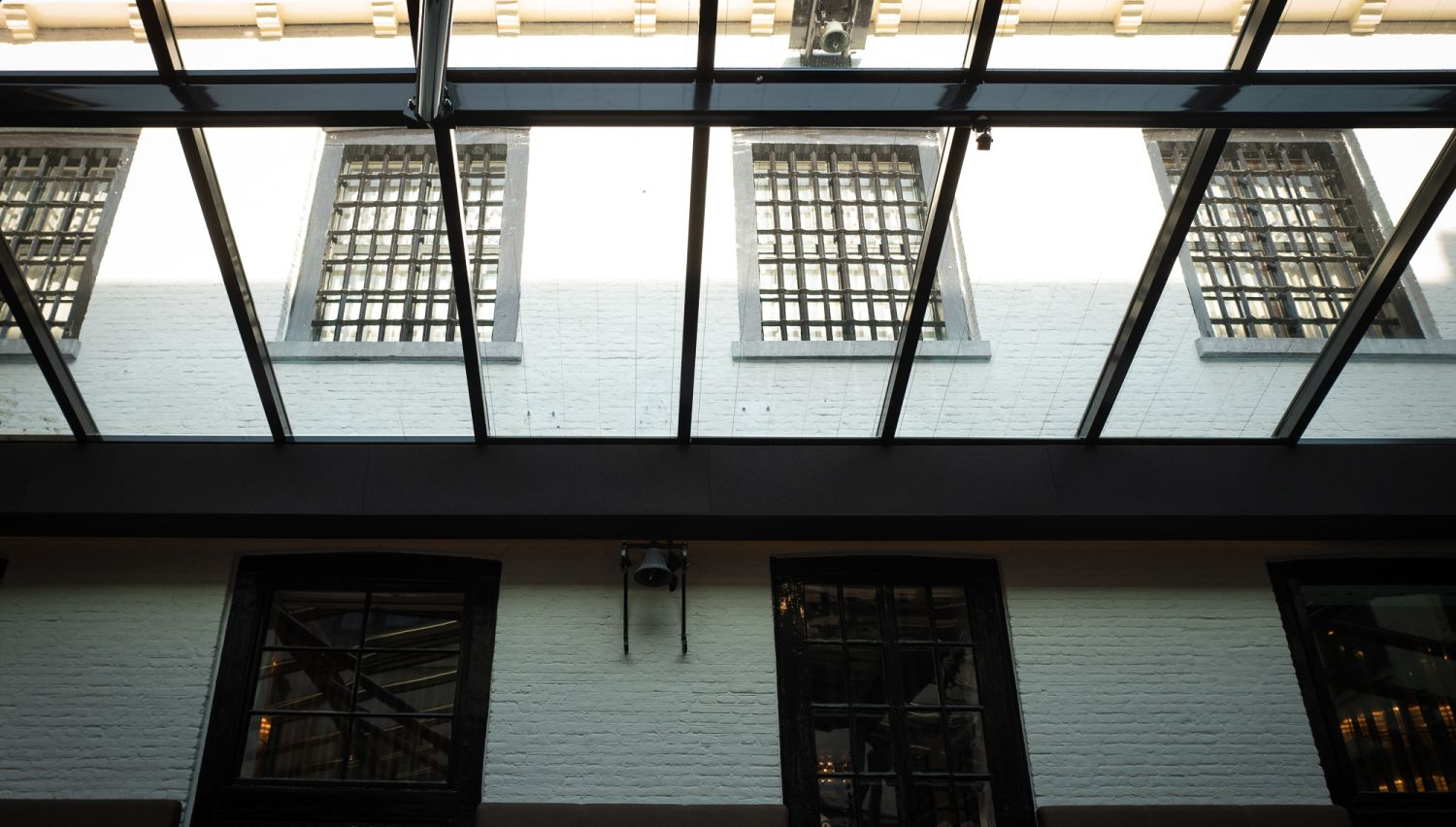 Glass covered courtyard with prison bars on the upper floor windows.