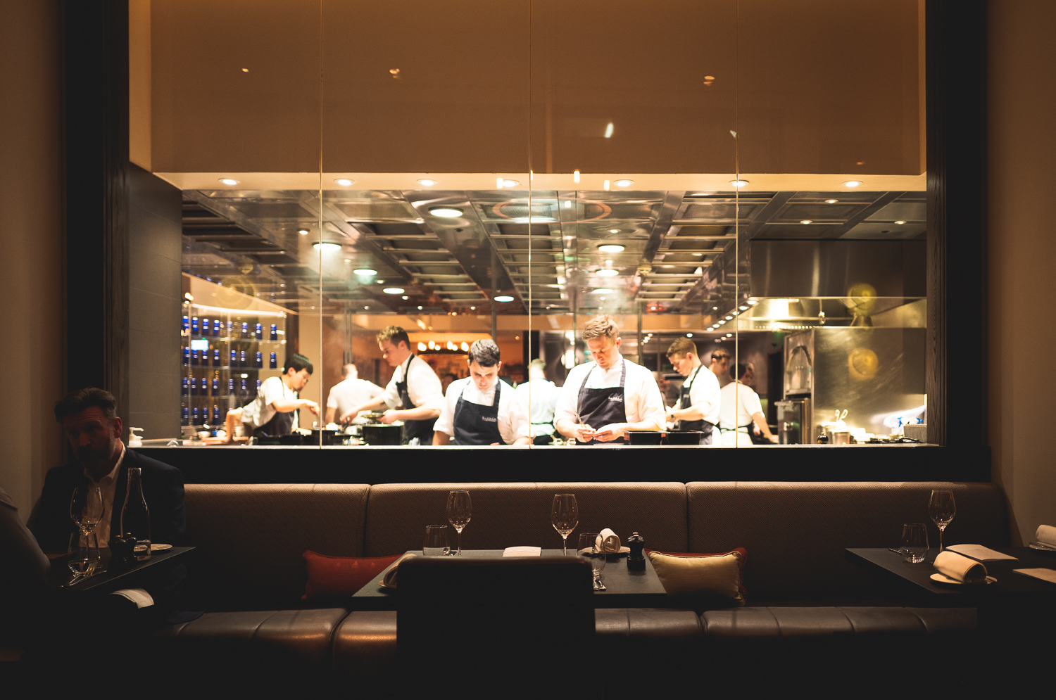 The chefs working away, visible from the dining area through a large pane of glass.