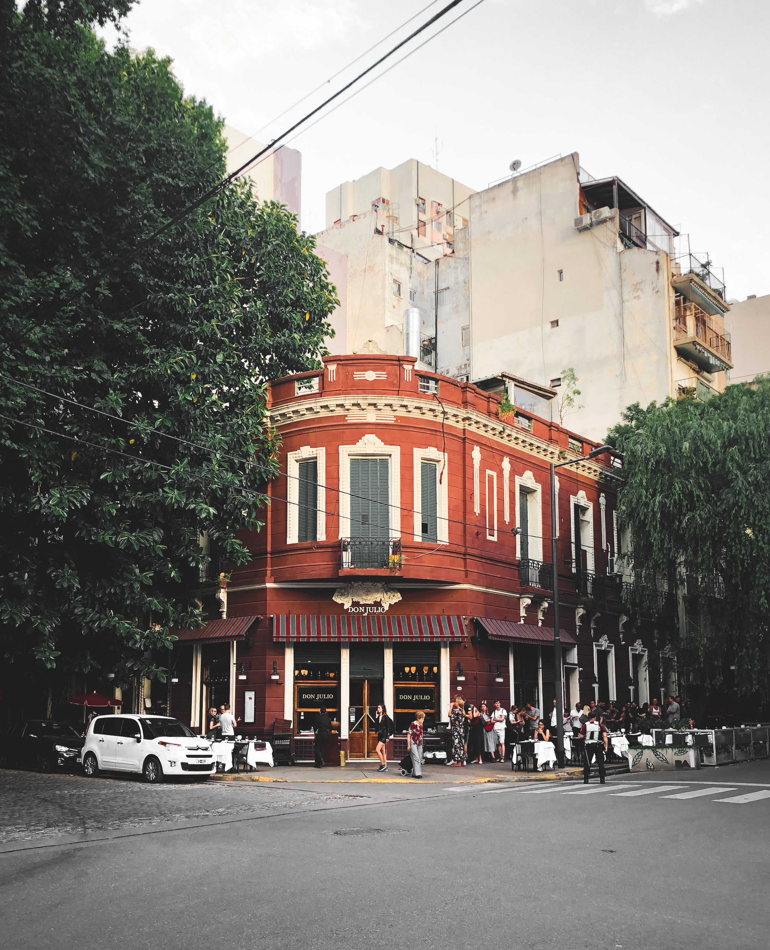 The corner of a red brick building two stories high flanked by tree-lined streets
