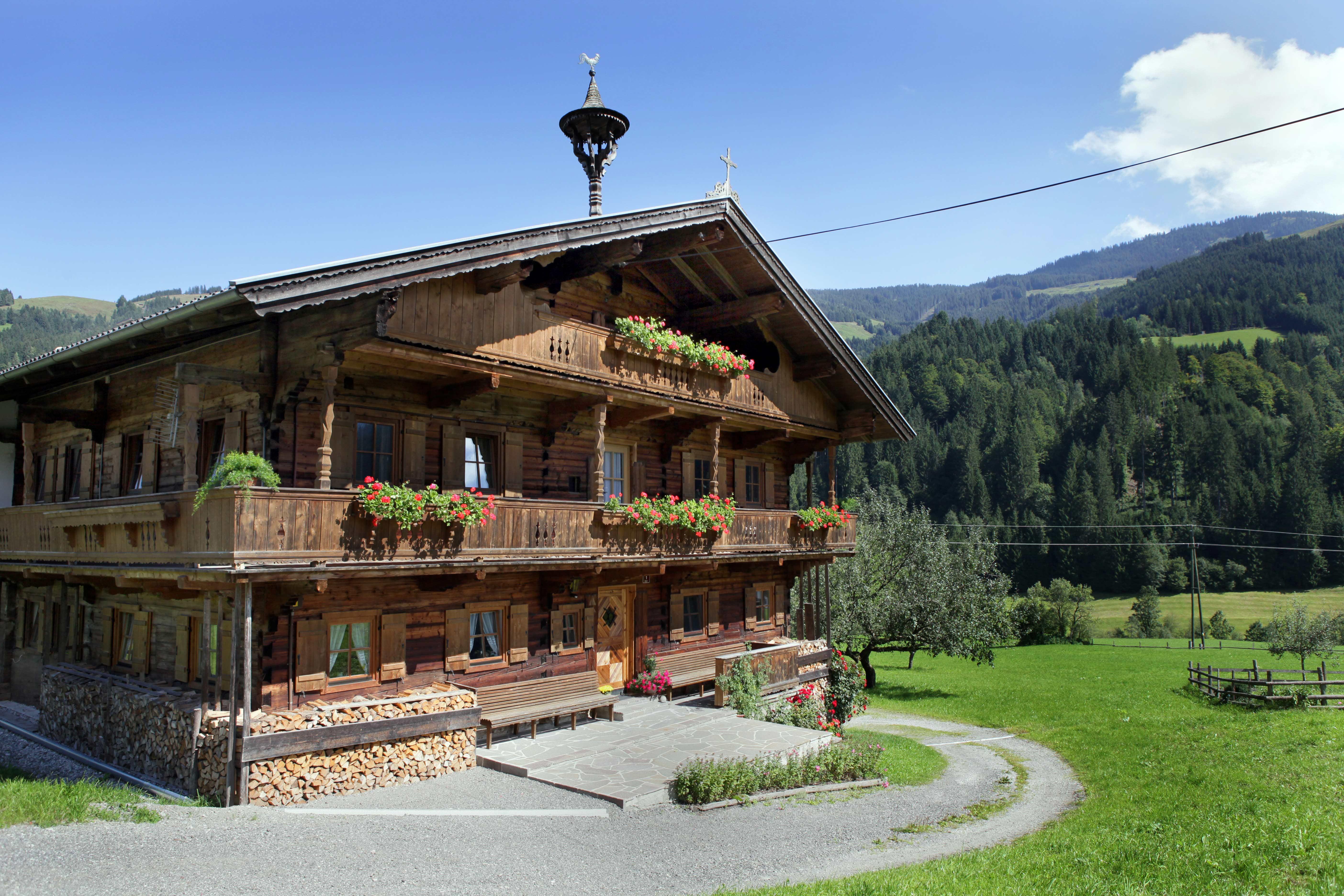 Een oud houten huis met bloemen in Kelchsau