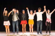 High school actors on staget bowing