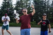 A student flies a drone while someone takes a photograph
