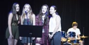 Teenage Girls Singing on Stage with Drummer