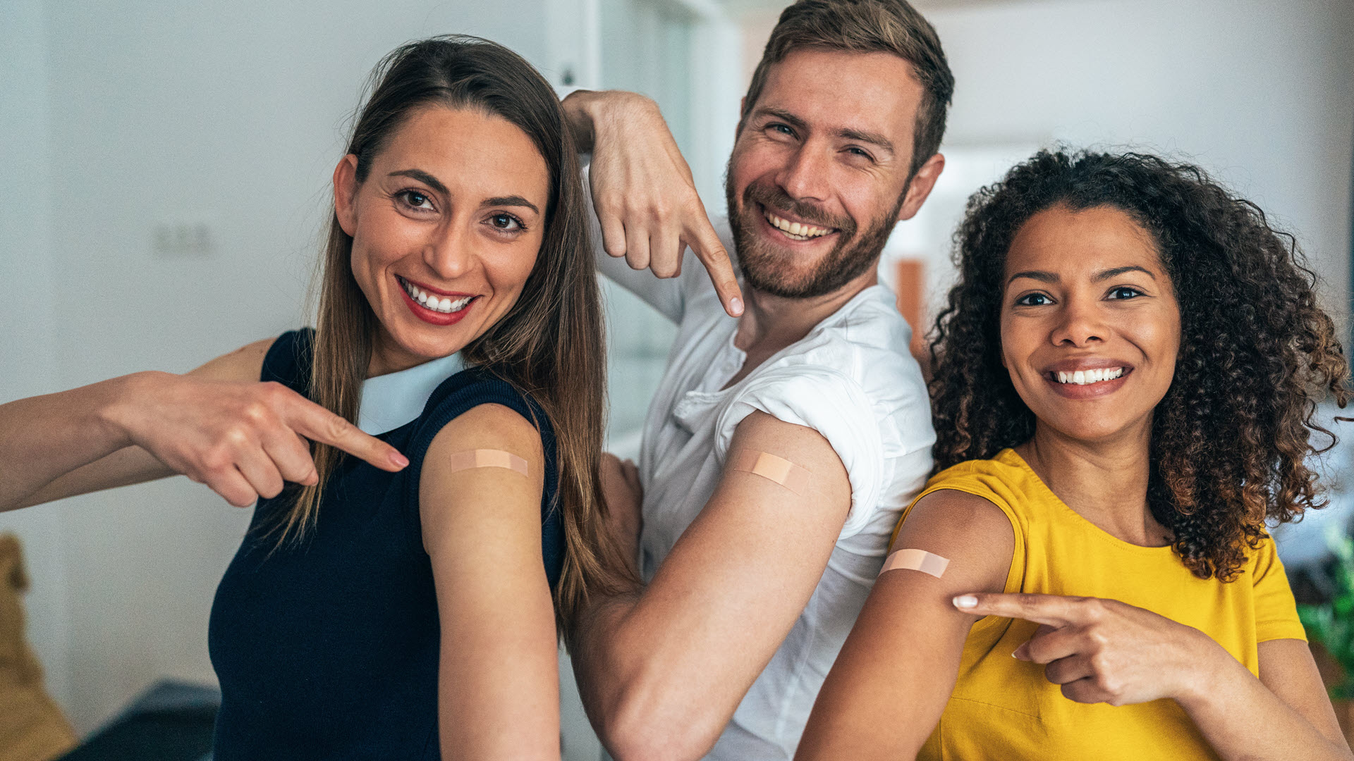 Friends in their twenties proudly showing they have been vaccinated
